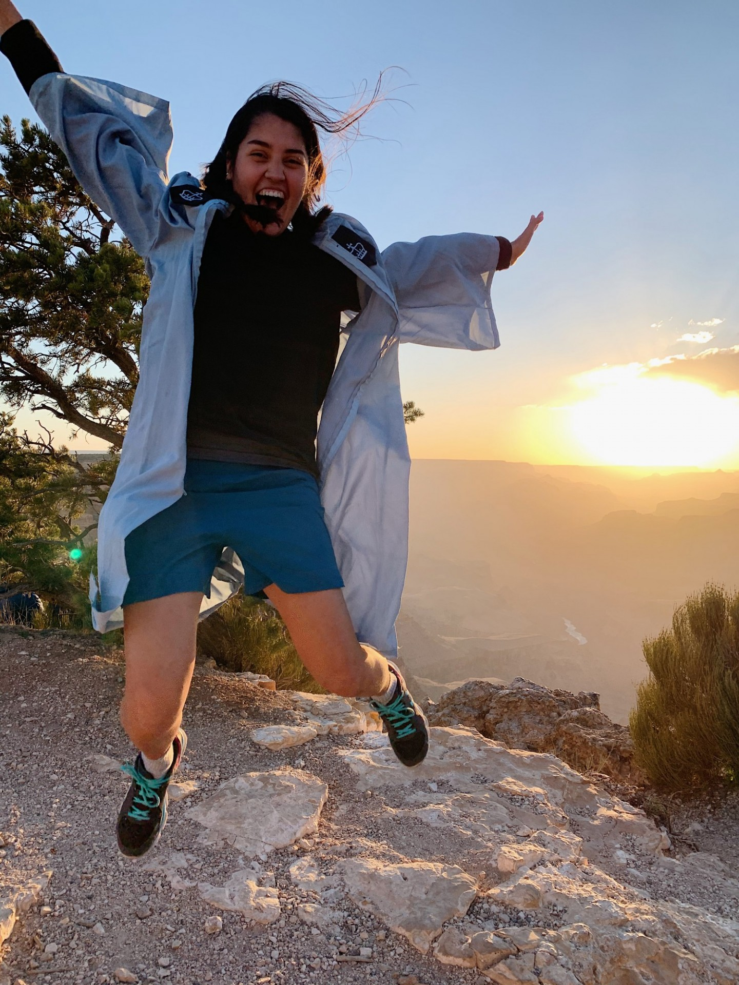 Celia Orduna jumps in Commencement regalia on the rim of the Grand Canyon.
