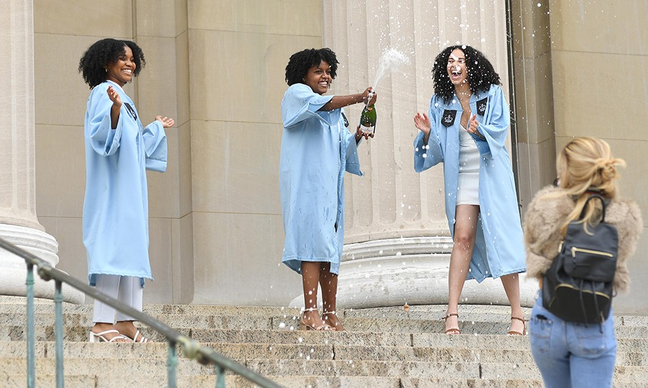 Three grads pop champagne on Low Steps while a photographer walks by.