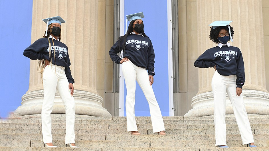 Three women in Columbia sweatshirts and mortarboards pose on Low Steps.