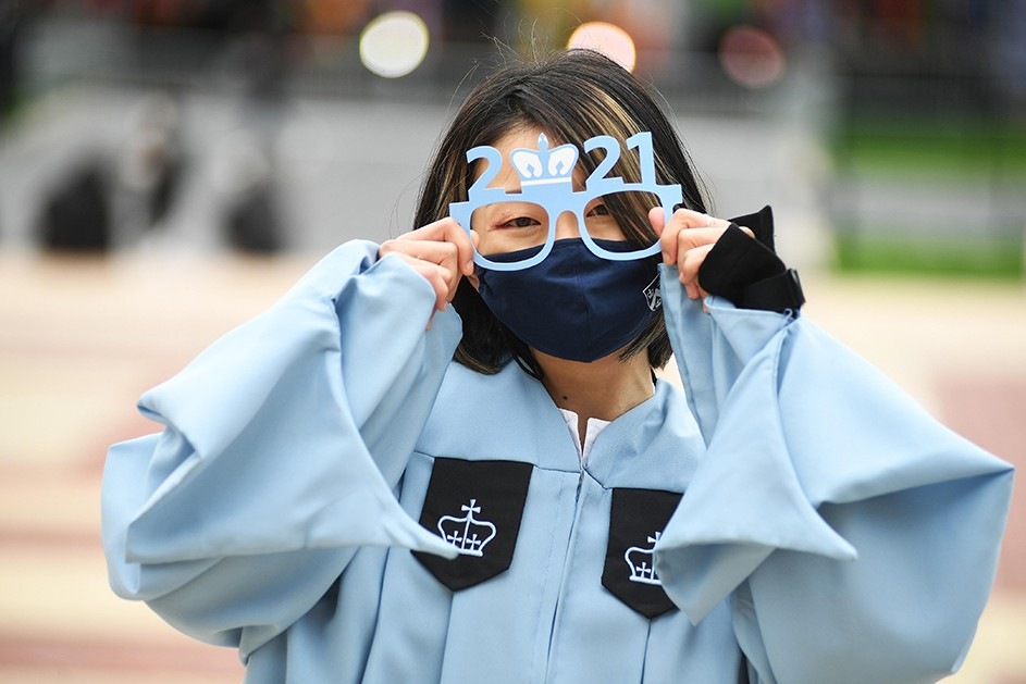 A woman in a blue robe holds up paper 2021 graduation glasses.