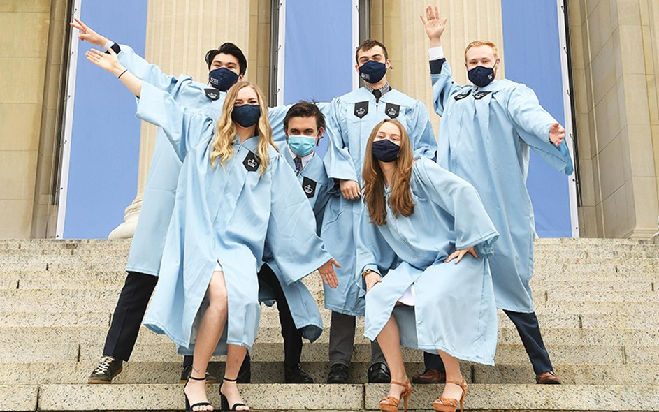 Masked Columbia grads in gowns pose on Low Steps.