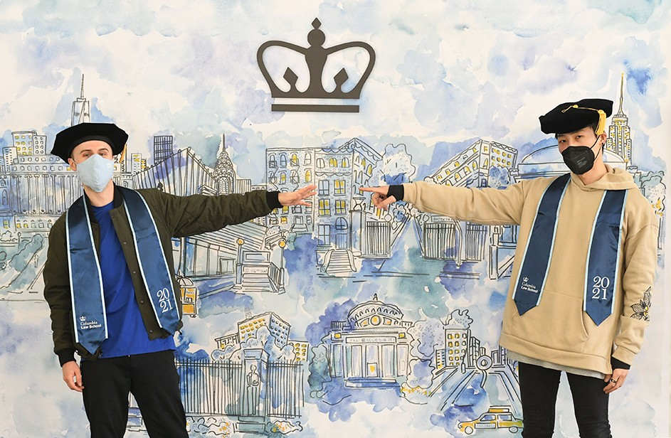 Two Columbia Law grads point ot a graphical representation of Columbia.