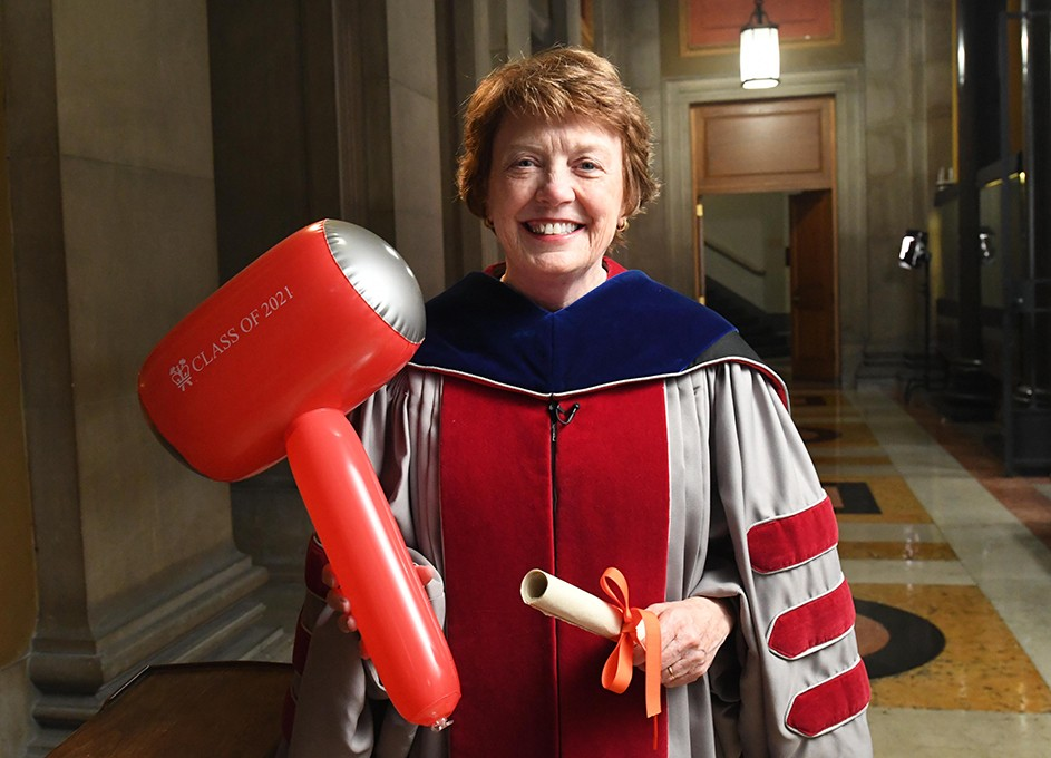 Mary Boyce in Commencement regalia with a hammer.