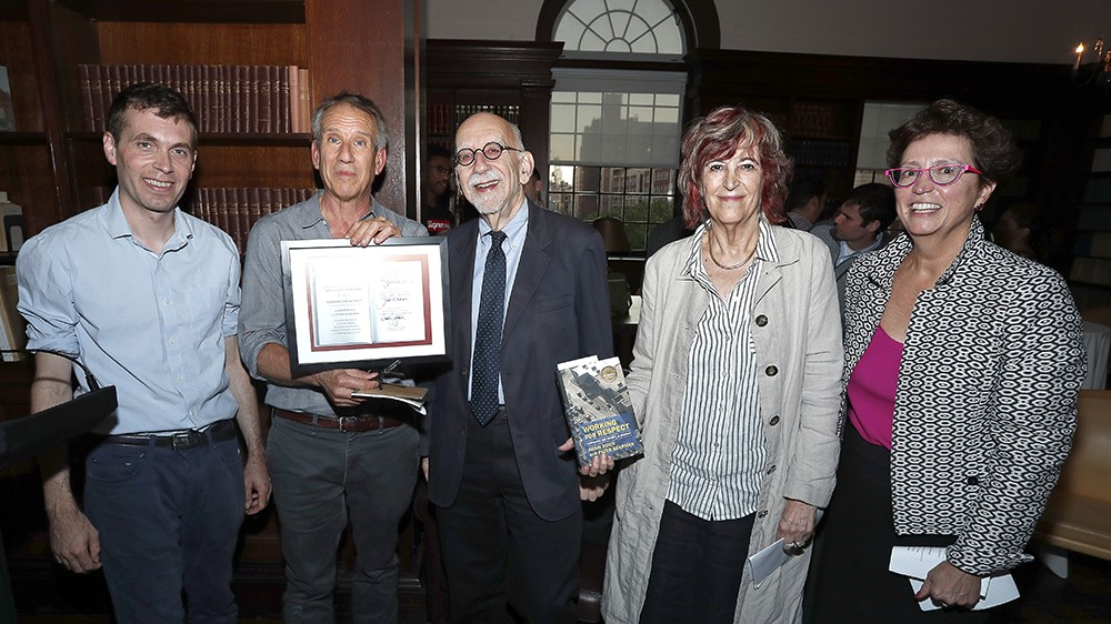 Five people posing for a photo with a book and a certificate