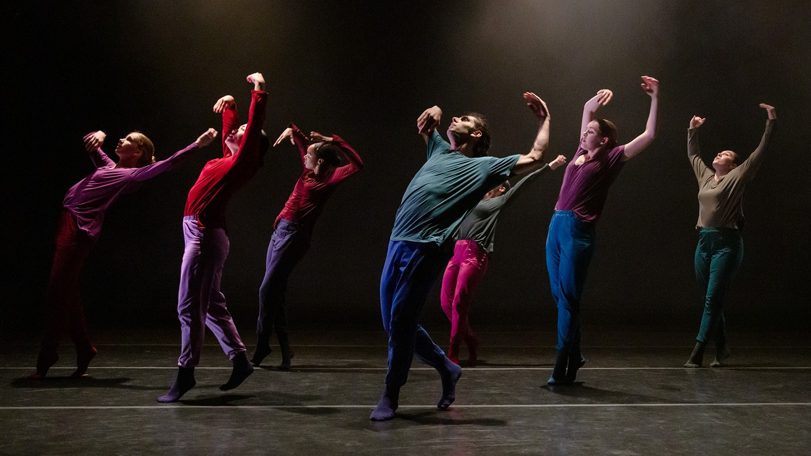 A group of dancers in multicolored clothing.