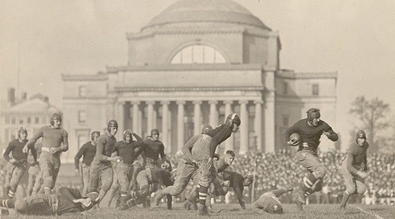 A group of men wearing old-fashioned uniforms and playing football in front of a classical building with steps.