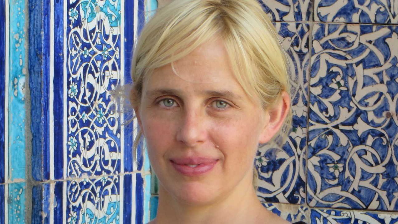 A woman with blond hair against a background of blue and turquoise Islamic tilework.