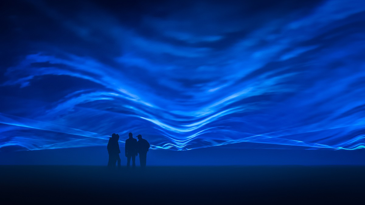 Four people standing among blue waves of light.