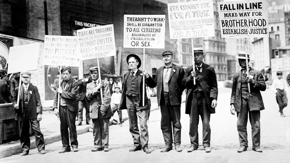 A black and white vintage photo from 1909 of a group of men dressed in jackets and ties walking on a New York City street men holding up protest signs about unemployment and the need for jobs.