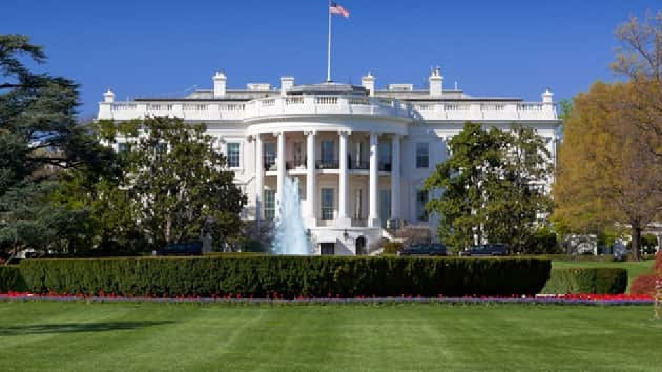The White house with an American flag flying on the roof and a fountain in the front lawn