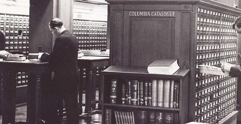 black and white vintage image of man standing at desk of columbia's butler library