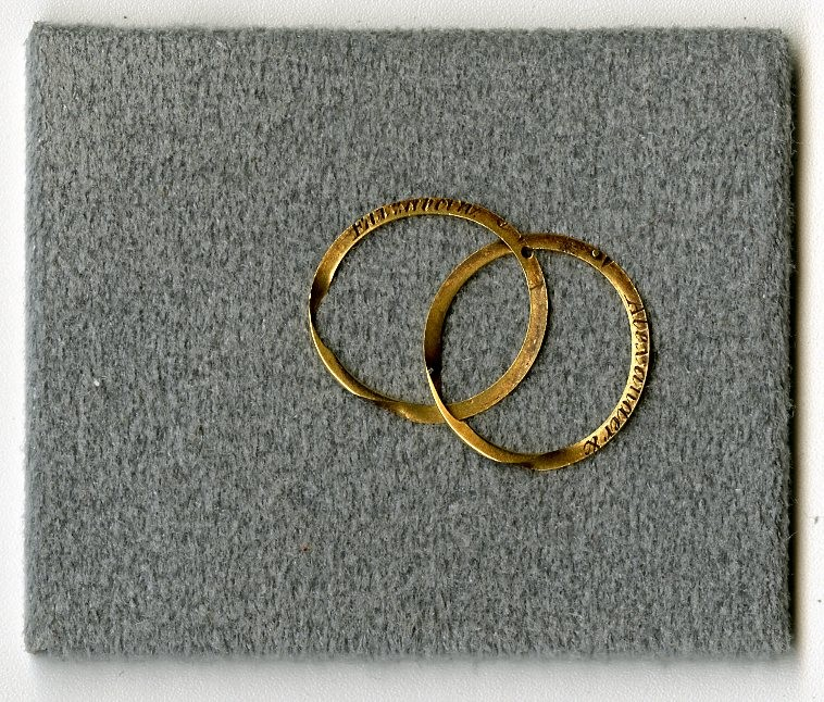 Two gold rings on grey background