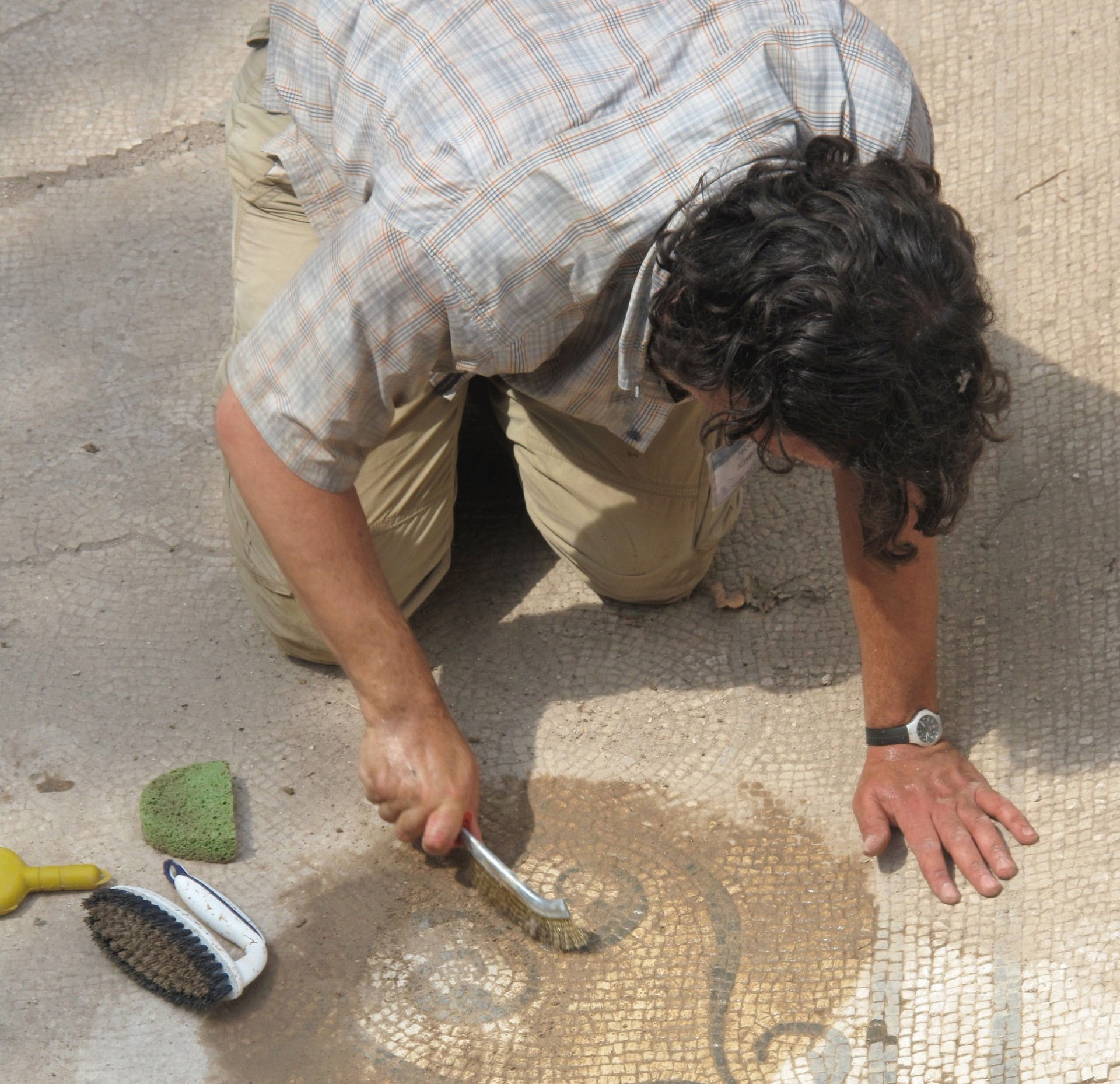 A man washes away dirt from a floor mosaic