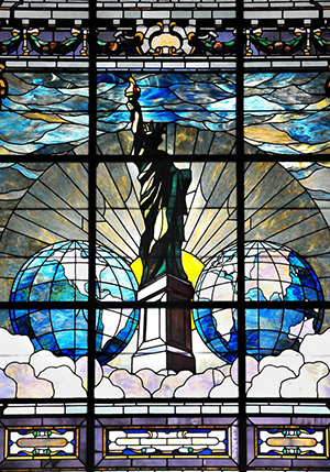 Stained glass window depicting two worlds and the Statue of Liberty on clouds in front of a rising sun.