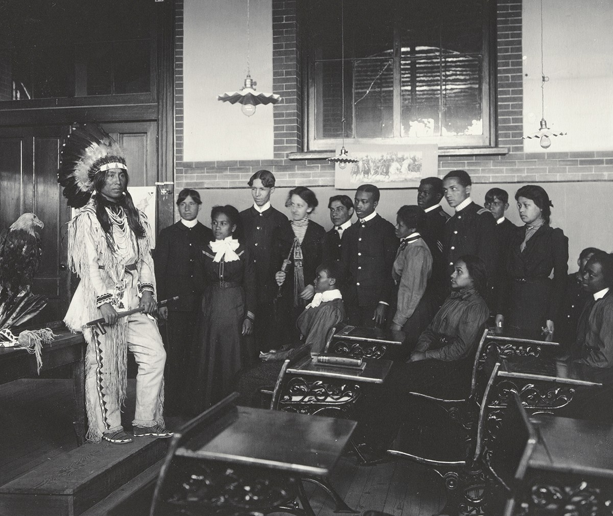 A Native American man wearing a feathered headdress stands in a classroom of students.