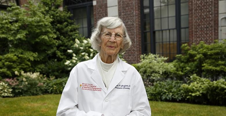 Dr. Sylvia Preston in a white lab coat stands outdoors in front of a green lawn