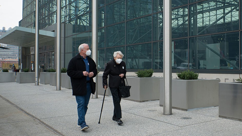 elderly man and woman wearing white masks walking on city sidewalk