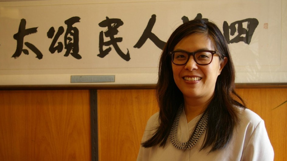 Eugenia Lean: A bespectacled Asian woman with long dark hair and wearing a white shirt and a beaded necklace, smiles in front of a framed piece of Chinese calligraphy