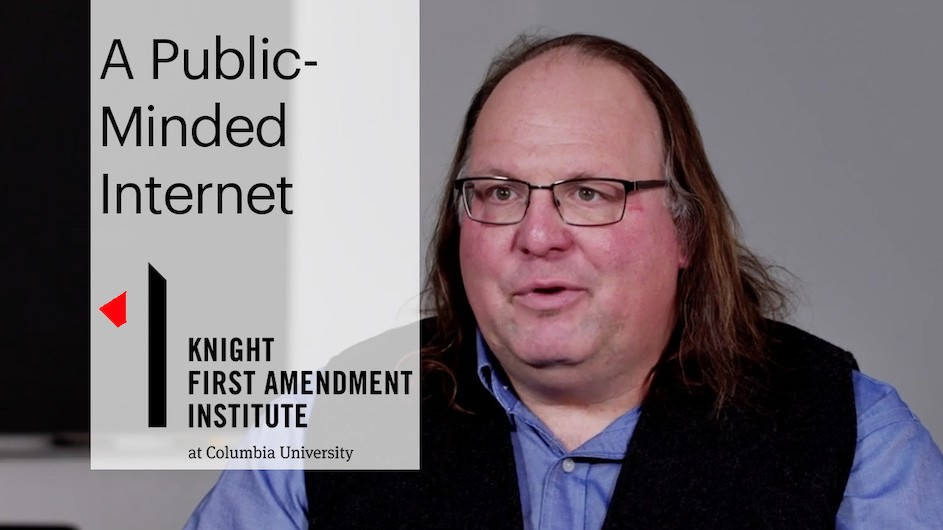 "A man with long hair and glasses on the right side of the frame with the text ""A Public-Minded Internet"" and ""Knight First Amendment Institute"" on the left"