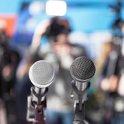 Photo of two microphones in front of a crowd