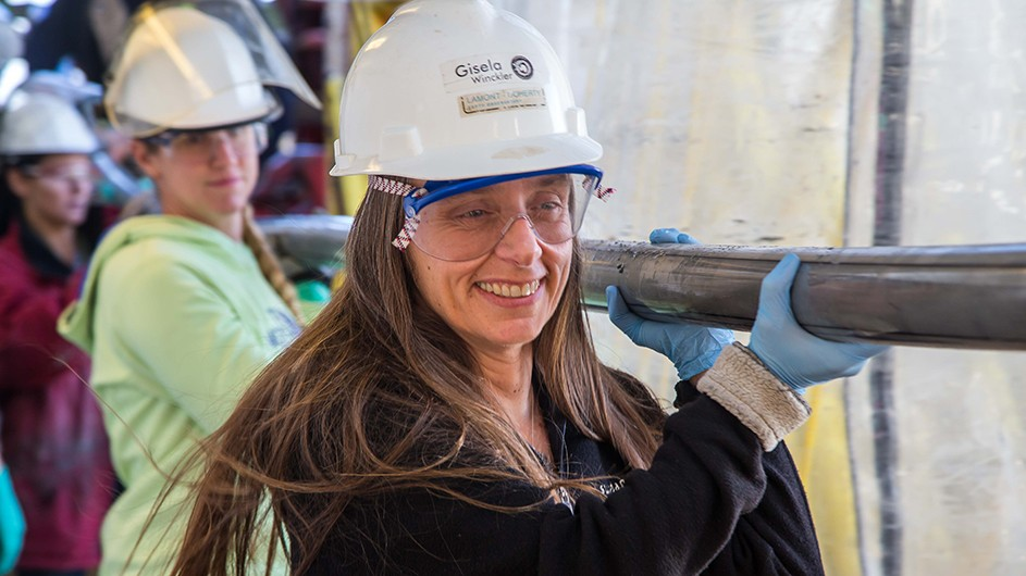 Smiling woman leading team in white hard hats on drill ship carrying think grey tubing