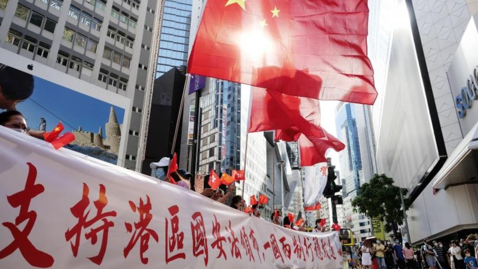 PRC flags are flown above a banner with Chinese characters.