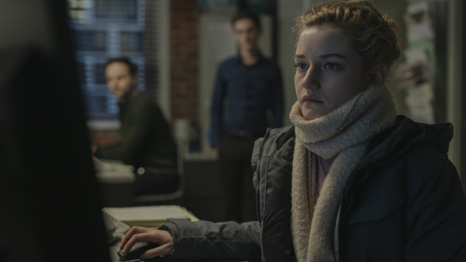 A woman wearing a white scarf sits in front of a computer with two men looking on.