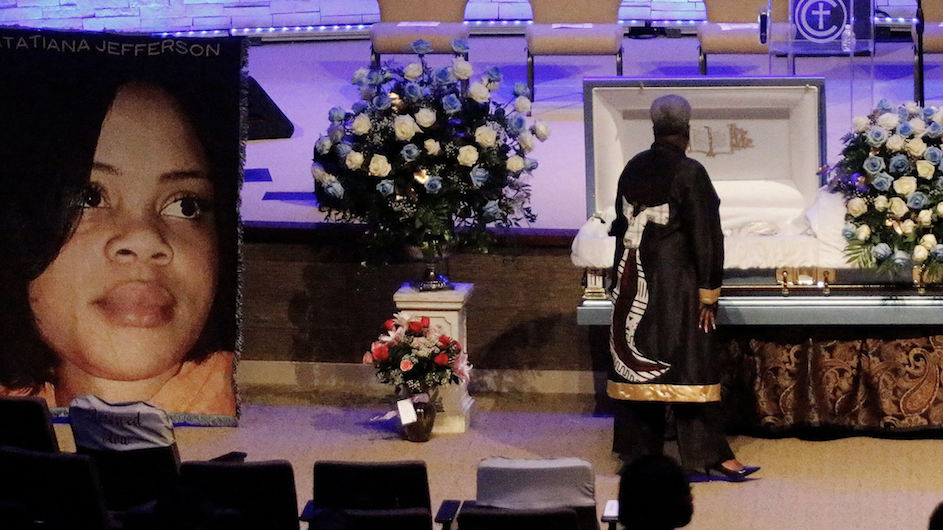 Large photo of a woman on the left side of the picture with a casket and flowers at the right side.