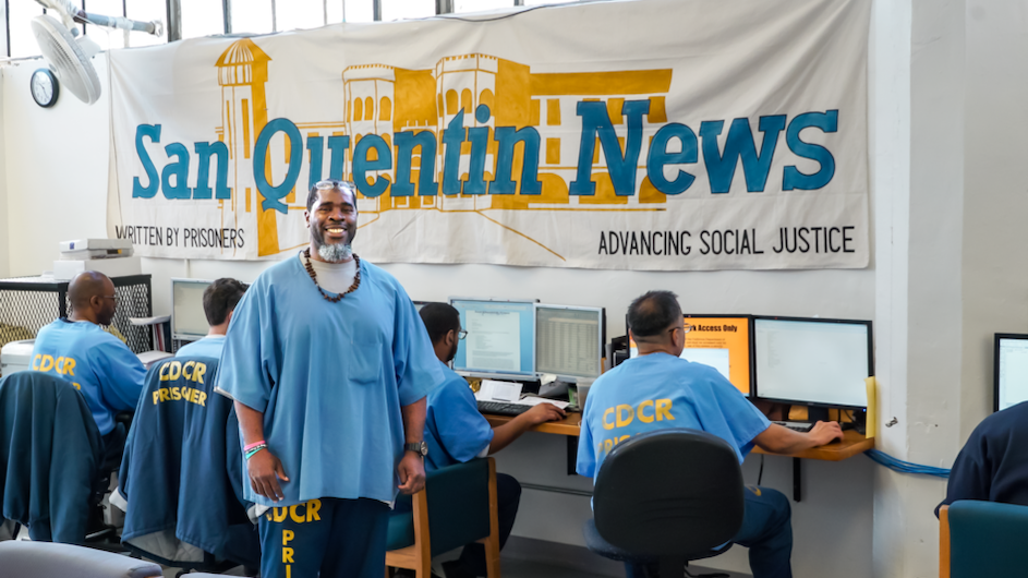 Man standing and smiling standing in front of people on computers and a banner saying San Quentin News
