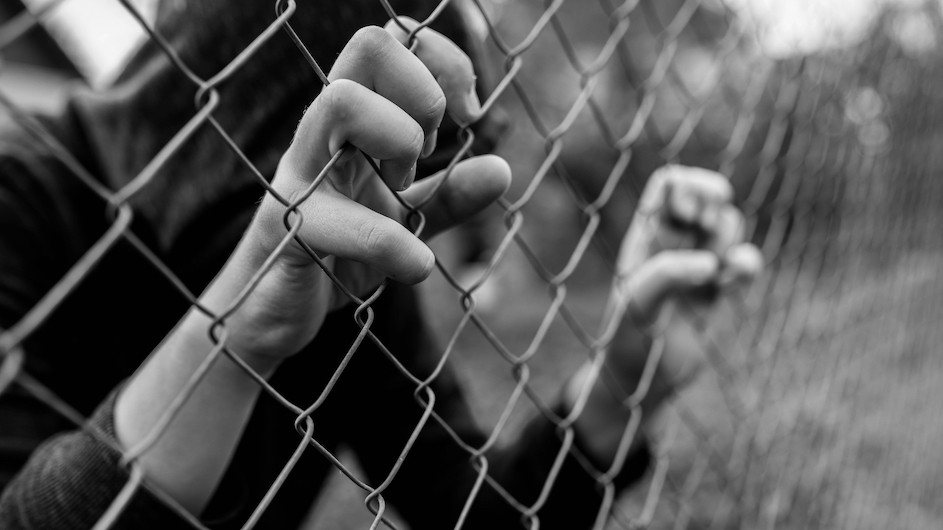 Black and white photo of a boy in a hoodie obscuring his face and he's holding onto a fence