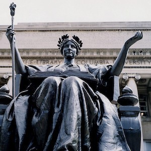 An image of a statue of a seated woman holding a mace in her right hand