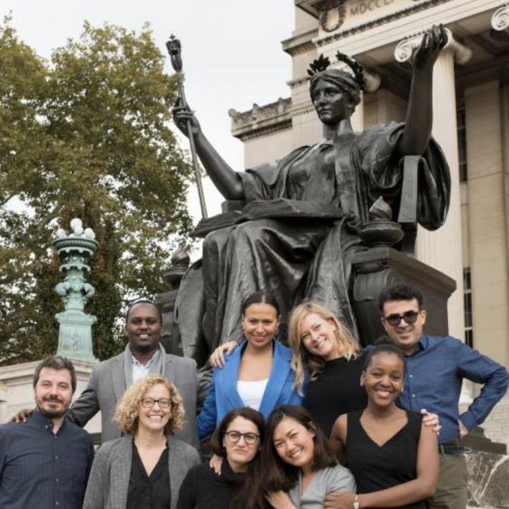 A group of people in front of a bronze statue of a woman with her arms out.