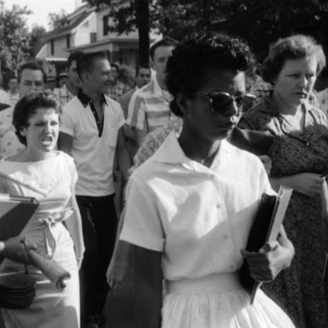 Black and white photo of a white woman yelling at a black woman with sunglasses. There are other people in the picture.