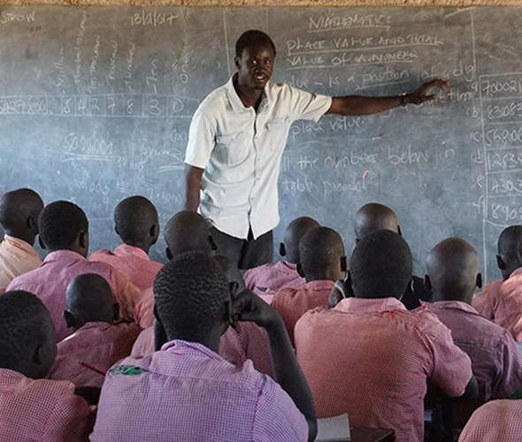 A teacher in white shirt at a chalkboard with writing on it stands in front of students with with red shirts and their backs to the camera.