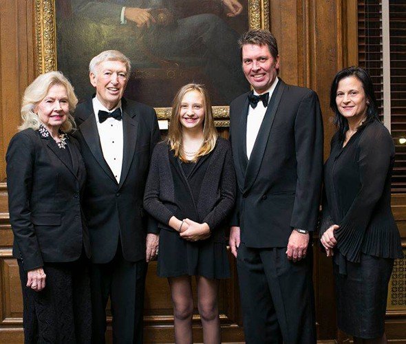 Five people dressed in black formal wear standing and posing in front of a picture