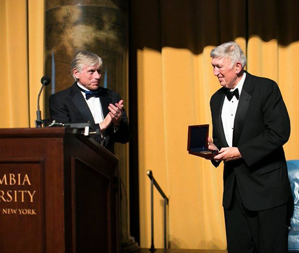 A man clapping at another man receiving an award