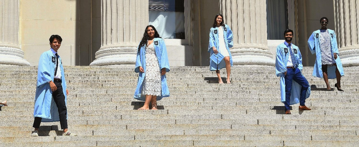 A diverse group of graduates in their Columbia gowns stand at a social distance on the steps of Low Library