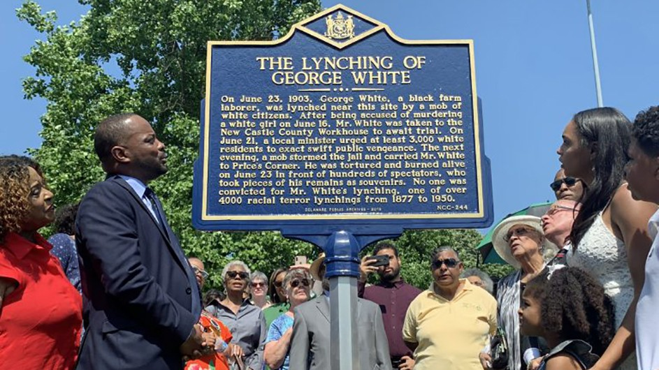 "A photo of a group of people looking at a blue plaque saying ""The Lynching of George White."" More text is under the title."