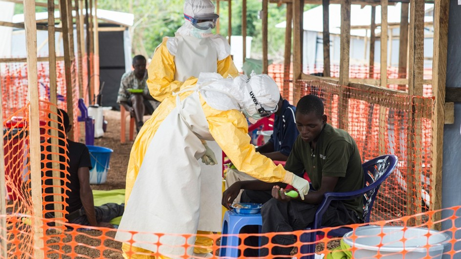 Two medics in yellow and white uniforms with protective eye and head gear treat an African young man with Ebola