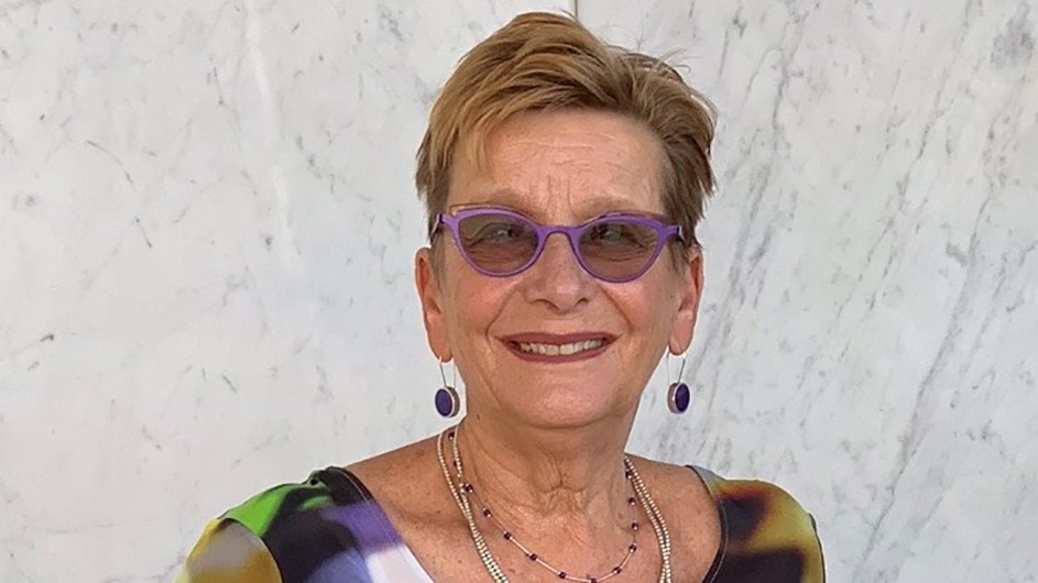 A woman with short blond hair wearing colorful glasses, shirt and jewelry faces the camera.