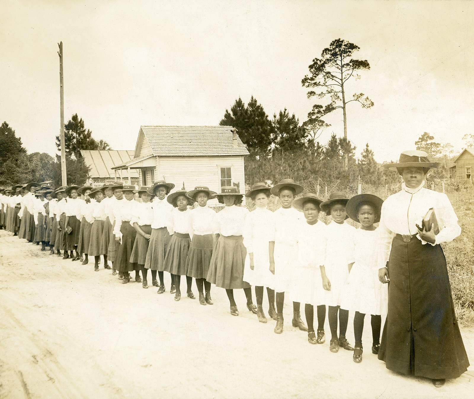A diagonal line of African American schoolgirls and their teacher.