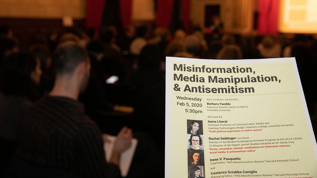 "Audience in background with a handout saying ""Misinformation, Media Manipulation, & Antisemitism"" in foreground"