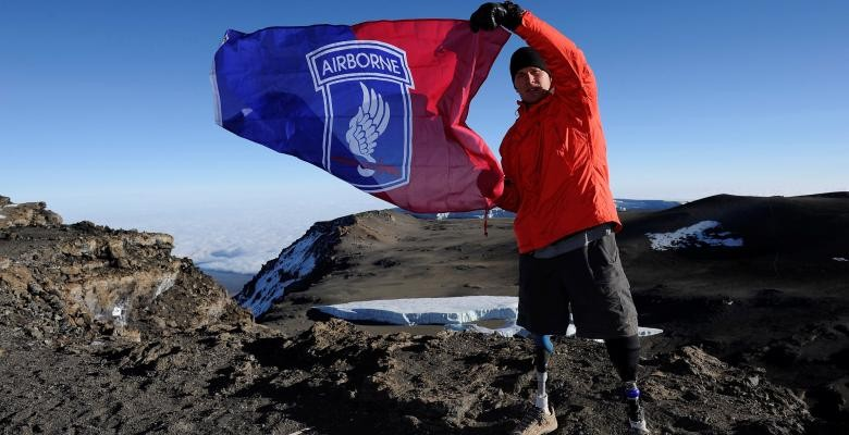 neil duncan waving a red and blue flag while standing atop a mountain dressed in red jacket and dark bottoms