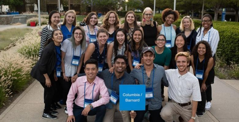 "A group of roughly two dozen people poses on a sidewalk with a placard reading ""Columbia/Barnard"""