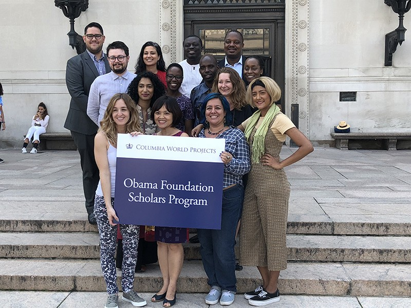 "A group of 14 women and men stand on the steps in front of Butler Library. The front row of three women holds a placard reading ""Columbia World Projects, Obama Foundation Scholars Program."""