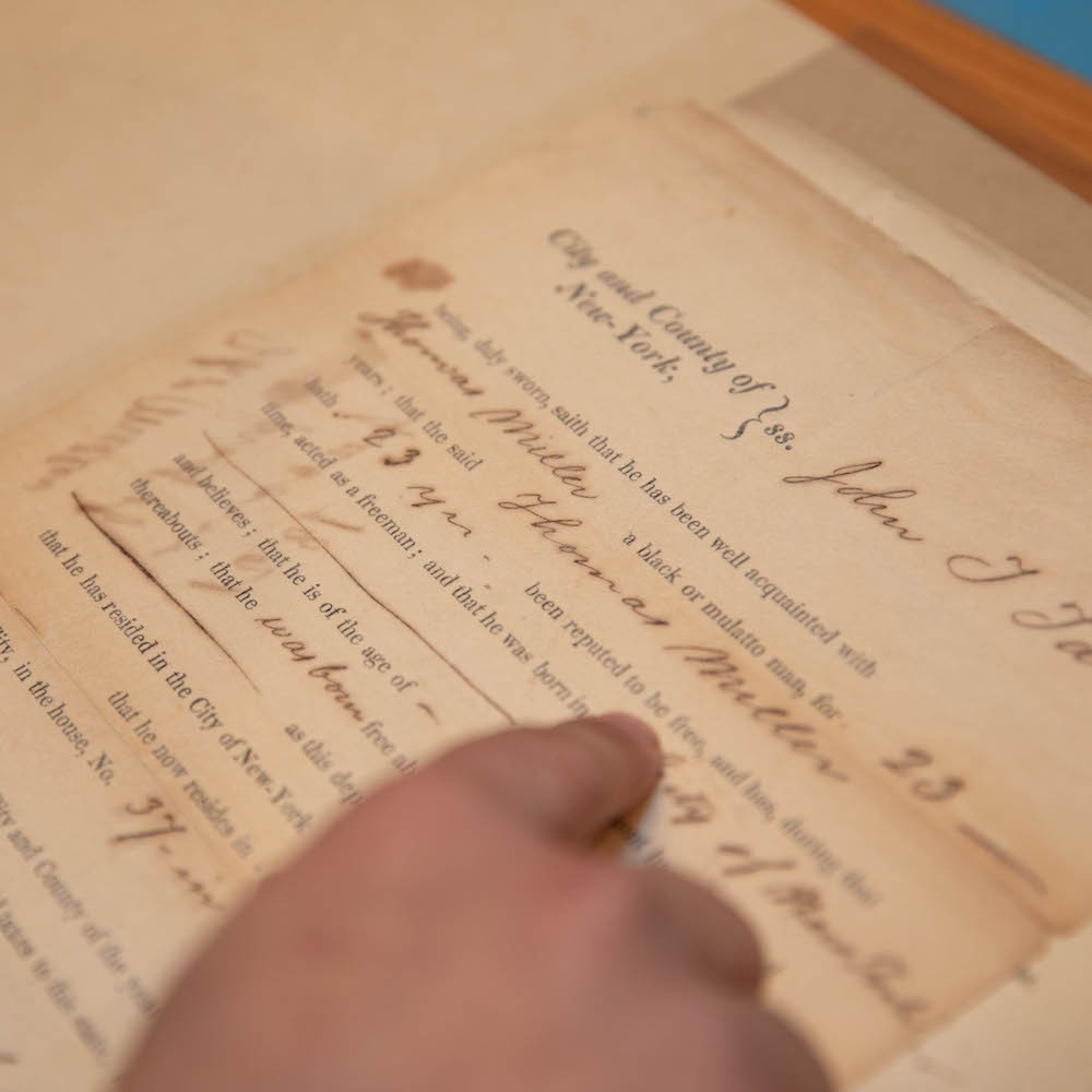 Hand pointing to the word free on an old document