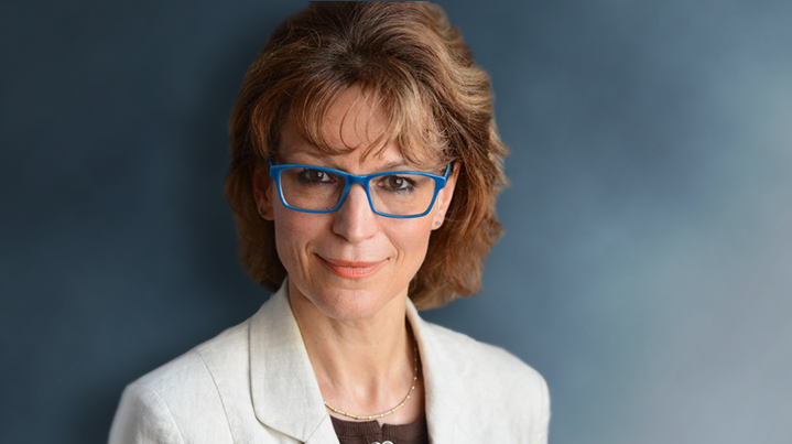 Agnes Callamard in blue glasses, a white jacket in front of a blue background.