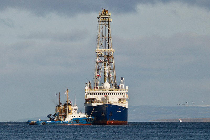 A research vessel with a tower on it is pulled by a tugboat on the ocean.