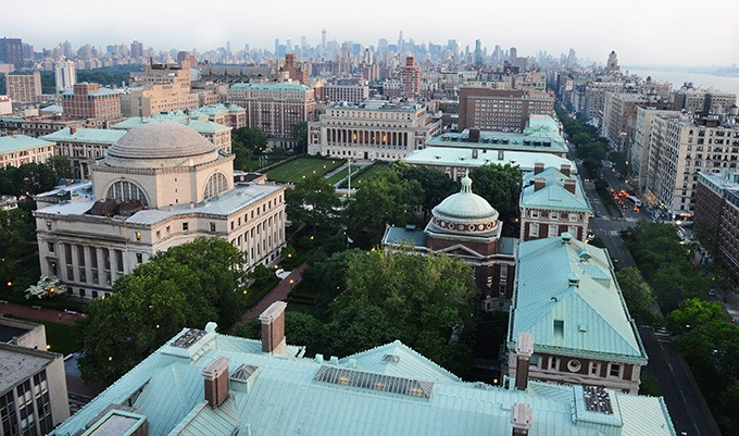 An aerial view of the Morningside Campus. The dome-shaped roof of Low Library risinig above full trees and the New York City skyline faded in the backdrop of the photo.