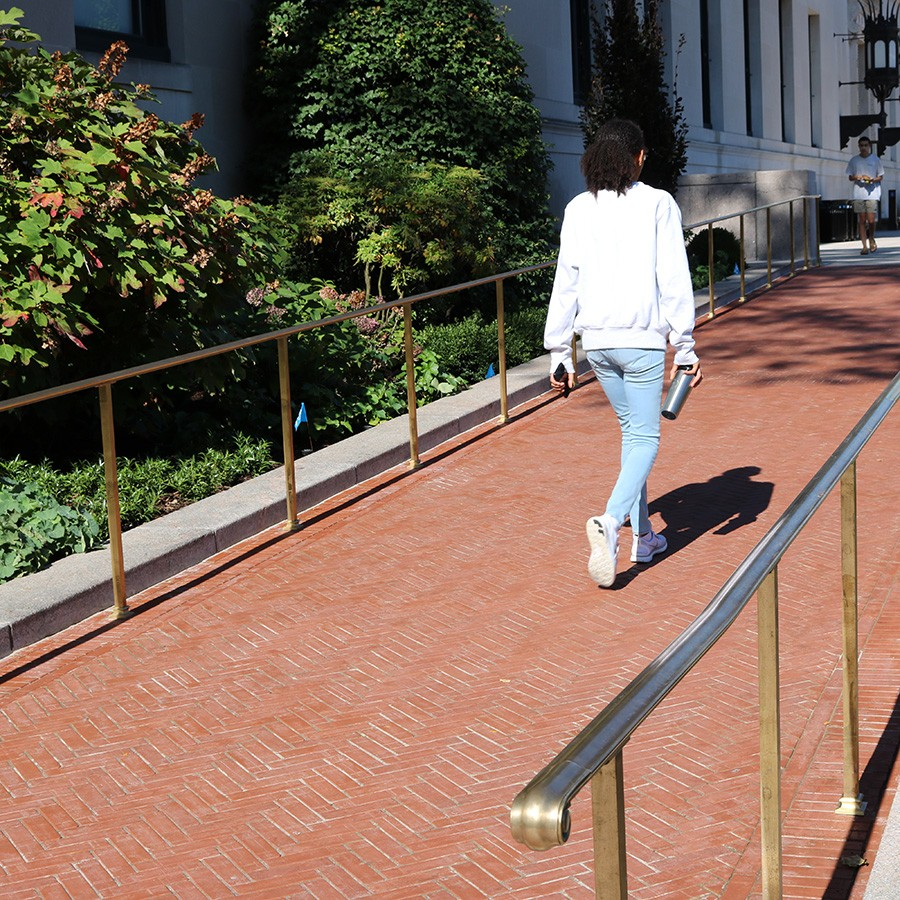 A young woman walks up a masonry ramp with bronze rails that leads up to the Butler Library North entrance.